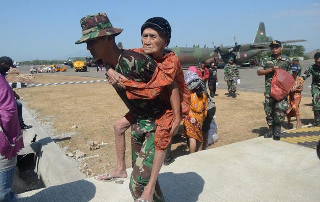Binh sĩ Indonesia cõng một cụ già đi sơ tán. (Ảnh: Reuters)