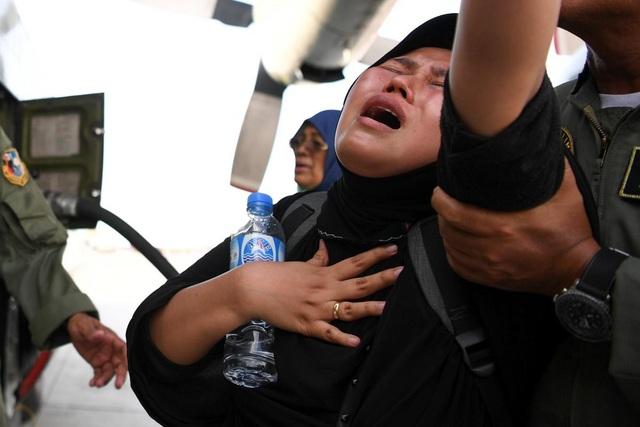 Một phụ nữ bật khóc khi được đội cứu hộ đưa lên máy bay di tản khỏi khu vực bị ảnh hưởng bởi động đất/sóng thần (Ảnh: Reuters)