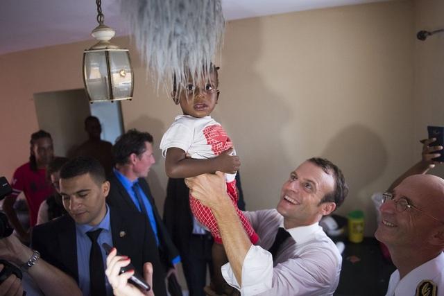 Tổng thống Macron bế một em nhỏ khi tới thăm các gia đình tại Saint Martin sau bão Irma (Ảnh: RT)