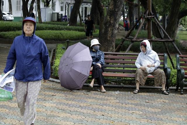 Người già ra đường trong trang phục ấm áp.