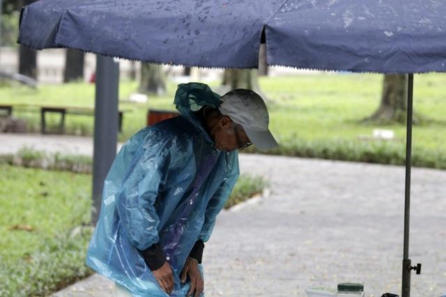 Một cụ già mặc thêm áo mưa để chống rét.