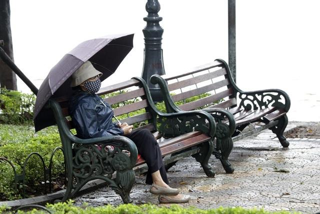 Một cụ già mặc áo ấm ngồi nghỉ ven bờ hồ Hoàn Kiếm.