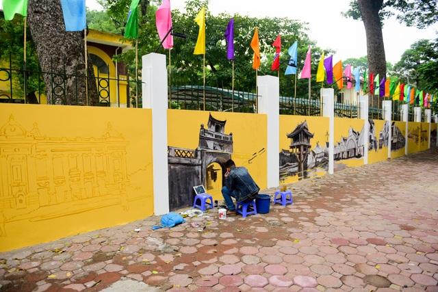 Để kỷ niệm 45 năm thành lập trường THPT Phan Đình Phùng, bức tường rào mặt phố cùng tên được vẽ tranh bích họa tạo khung cảnh khá đẹp mắt.