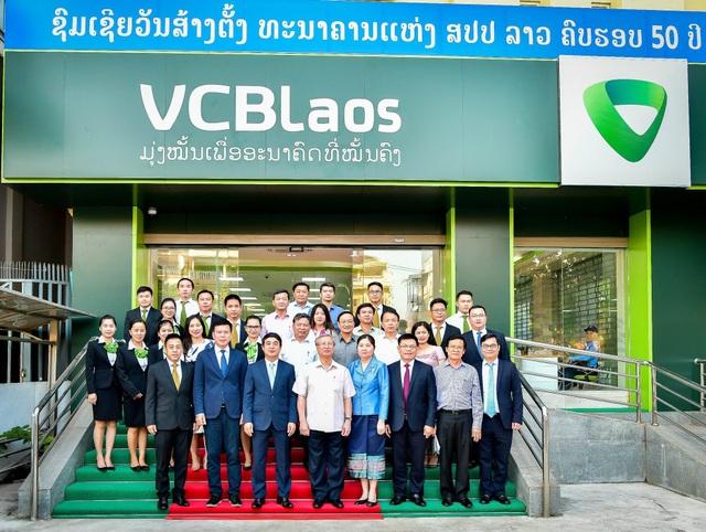Đ/c Trần Quốc Vượng, Ủy viên Bộ Chính trị, Thường trực Ban Bí thư Trung ương Đảng CSVN (thứ 4 từ trái sang, hàng thứ nhất) chụp hình lưu niệm với Đại diện Ban lãnh đạo Vietcombank, Ban giám đốc và cán bộ nhân viên Vietcombank Lào trước Trụ sở Vietcombank Lào tại Viêng Chăn.