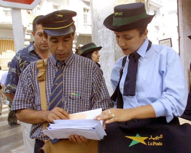 Một nữ nhân viên bưu chính và đồng nghiệp nam đang làm việc tại Rabat, Ma Rốc. Lần đầu tiên ở quốc gia này, 68 phụ nữ làm nhiệm vụ đưa thư ở 16 thành phố.