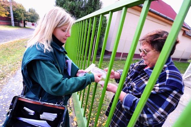 Nhân viên bưu chính Bernadett Kasza thuộc ngành bưu điện Hungary đang chuyển tiền tận tay tới một khách hàng ở thủ đô Budapest. Nữ nhân viên này từng nhận giải thưởng Viên chức Bưu chính xuất sắc nhất năm 2012.
