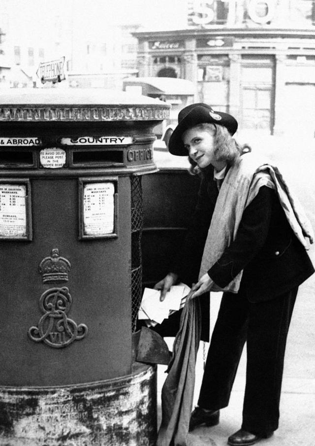Nụ cười hút hồn của một nữ nhân viên bưu chính ở London, Anh, khi đang lấy thư từ trong hòm. Ảnh chụp ngày 30/11/1942. Vào thời điểm đó, do nam giới tham gia vũ trang và các nhà máy sản xuất, nên trong ngành bưu chính phần lớn là nữ giới.