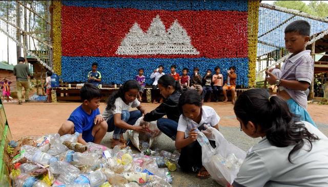 Học sinh của Trường Rác học cách phân loại rác thải. Đằng sau các em là quốc kỳ Campuchia được xếp bằng nắp chai nhựa. (Ảnh: AFP)