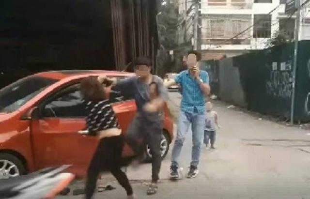 Người dân đã quay clip chồng đánh đập vợ trên phố Trần Quốc Hoàn rồi đưa lên mạng xã hội (Ảnh cắt từ clip)