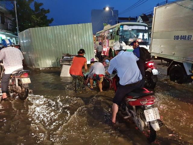 Người dân Sài Gòn giúp nhau trong những ngày triều cường dâng cao (trong ảnh một cô gái bị ngã xe khiến đồ đạc bị ướt hết)