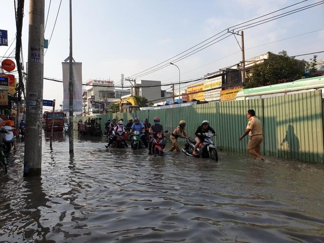 Cảnh sát giao thông giúp dân đẩy xe qua điểm ngập.
