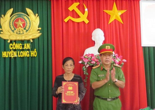 Đại tá Trần Văn Thắng, Trưởng Công an huyện Long Hồ trao quyết định thăng cấp bậc hàm của cho mẹ Trung úy Nguyễn Đức Đạt.