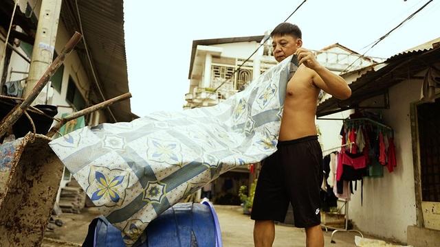 Ông Trần Văn Hòa đang trải bạt phủ lại cuộn dây dẫn nước