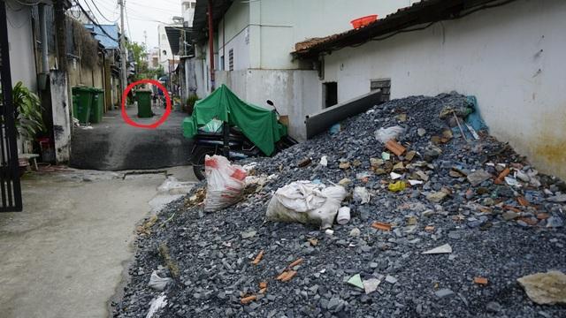 Đống xà bần ông Hòa gom về chuẩn bị cho việc nâng nền. Phía xa, chỗ vị trí khoanh tròn là miệng hố ga điều tiết nước cho máy bơm được người dân đánh dấu bằng thùng rác