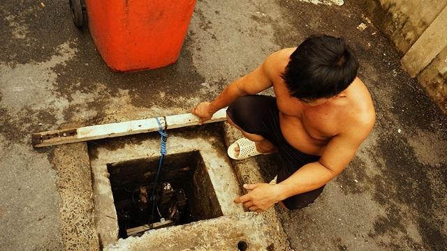Ông Hòa đang kiểm tra lại hố ga chính vì nước vẫn còn xâm xấp, mặc dù không có triều cường hay mưa lớn