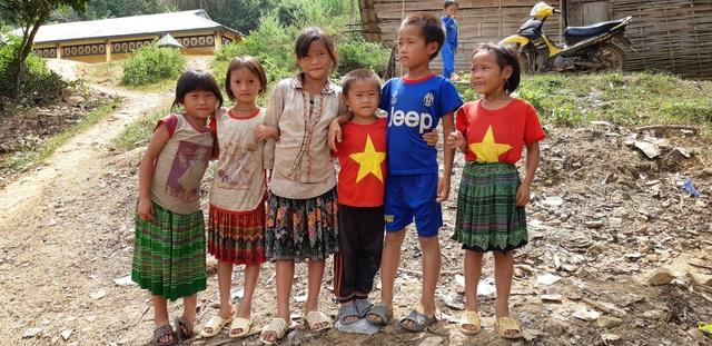 Bọn trẻ lấy làm sung sướng khi có đoàn tặng cho những chiếc áo in hình là cờ tổ quốc