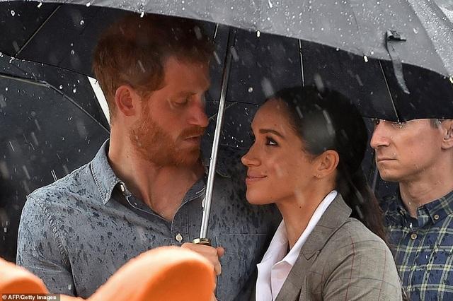 Hoàng tử Harry và cựu diễn viên điện ảnh Meghan Markle cùng che ô đứng dưới mưa