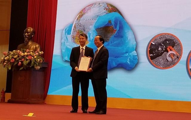 Ông Phạm Duy Hưng - GĐ Pháp lý và Đối ngoại FrieslandCampina VN (trái) trao cam kết chống rác thải nhựa cho ông Võ Tuấn Nhân – Thứ trưởng Bộ TNMT