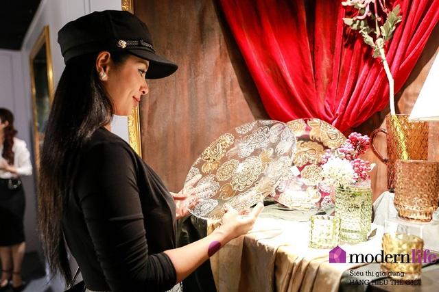 Cựu người mẫu Thúy Hằng chăm chú xem bộ đĩa thủy tinh nạm vàng thủ công trong triển lãm.