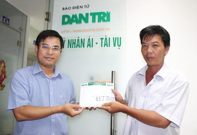 Anh Lưu Sinh Hết (bên phải) xúc động nhận sự giúp đỡ của bạn đọc Dân trí