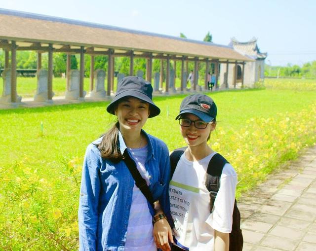 2 nữ sinh viên rạng rỡ bên khung cảnh đẹp cổ kính với hàng rùa đội bia tiến sĩ ở Văn Thánh Huế