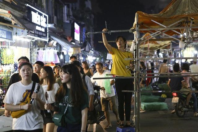 Những ki-ốt bán hàng đang được dựng lên tại khu chợ đêm. Tại đây nhịp điệu buôn bán rộn ràng của người mua kẻ bán kéo dài đến 24h.