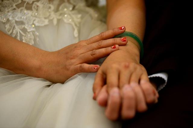 Những cái nắm tay chặt của 1 cặp vợ chồng trong lúc chờ làm lễ.