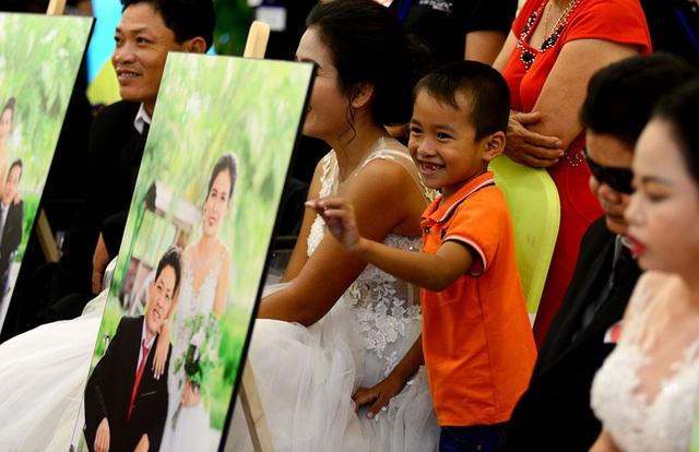 Cậu bé thích thú với tấm hình cưới của cha mẹ mà lần đầu cậu được nhìn thấy.