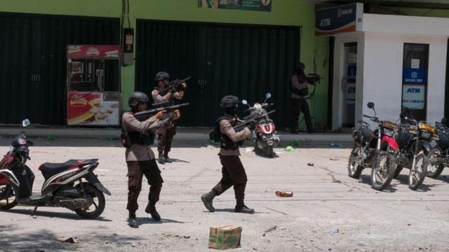 Cảnh sát Indonesia buộc phải dùng súng để trấn áp đám đông muốn xông vào một cửa hàng (Ảnh: BBC)