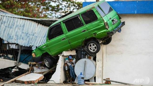Xe ô tô bị cuốn bay vào nhà dân sau thảm họa tự nhiên (Ảnh: AFP)