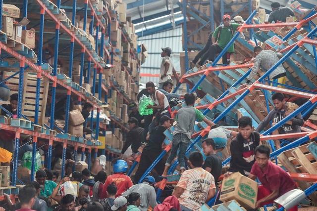 Người dân hôi của tại một nhà kho ở Palu sau thảm họa. (Ảnh: Reuters)