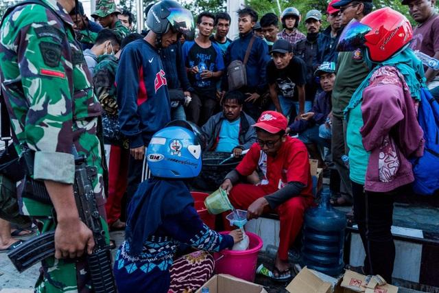 Các binh sĩ cầm súng giám sát người dân xếp hàng mua nhiên liệu (Ảnh: New York Times)
