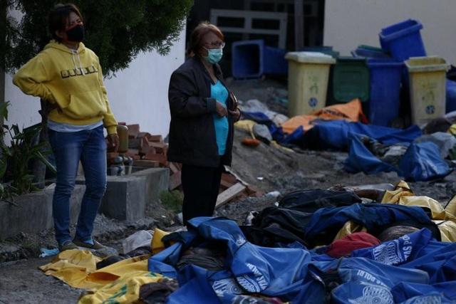Người dân Indonesia dáo dác tìm thân nhân trong những chiếc túi đựng thi thể nằm rải rác trên đường (Ảnh: Reuters)