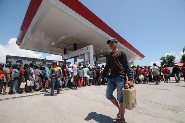 Hàng trăm người vẫn đang xếp hàng tại các trạm xăng tại Palu để mua nhiên liệu. Những đứa trẻ đứng giữa đường, cầm trên tay hộp xin tiền ủng hộ.