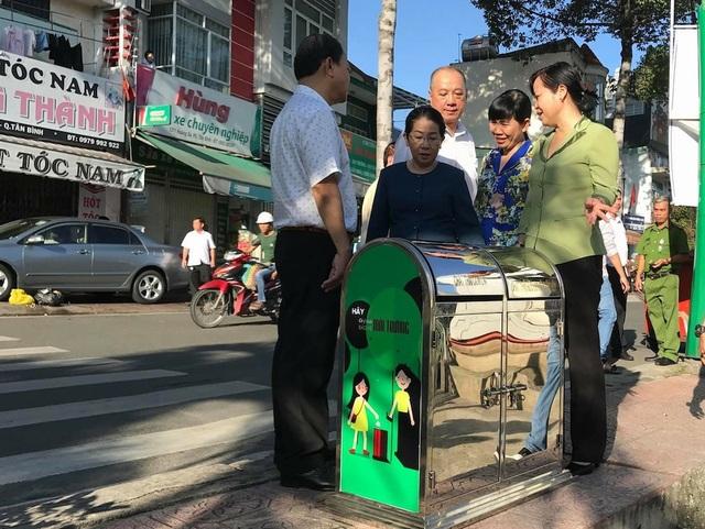 Phó Bí thư Thành ủy Võ Thị Dung (áo xanh ở giữa) tham dự chương trình và tặng thùng rác cho địa phương