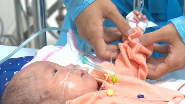 Dù mới chỉ 3 tháng tuổi nhưng cậu em Công Minh đã cảm nhận được hơi ấm từ bàn tay anh trai.
