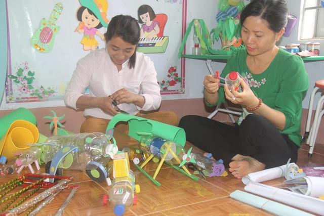 Tranh thủ sáng sớm, hai giáo viên trường mầm non Hoa Mai làm dụng cụ học tập cho học sinh.