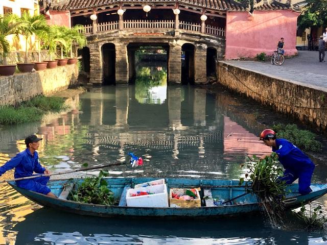 Công nhân đi vớt hoa đăng và rác ở khu vực Chùa Cầu