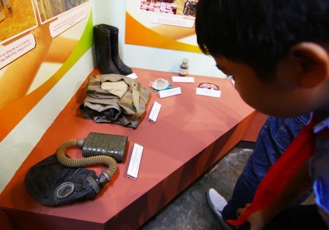 Một em học sinh nhìn không rời chiếc mặt nạ phòng khí độc sử dụng trong chiến tranh hóa học tại Việt Nam cách đây đã nửa thế kỷ