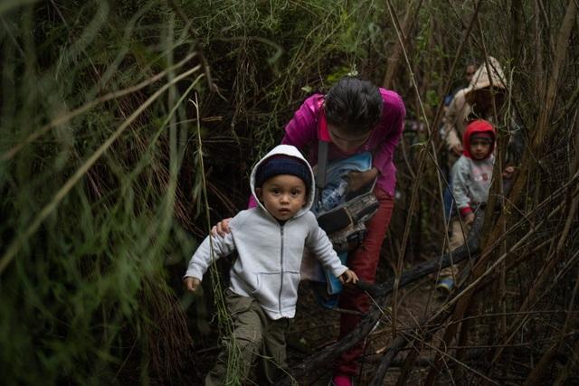 Một bé trai Honduras cùng mẹ đi qua bụi rậm khi tìm cách nhập cảnh trái phép vào Mỹ qua biên giới Mexico. (Ảnh: Reuters)