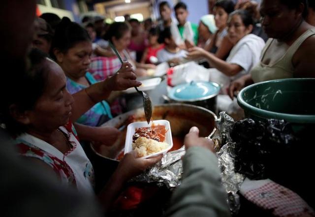 Các tình nguyện viên phát đồ ăn cho đoàn người tị nạn Honduras ở Guatemala. (Ảnh: Reuters)