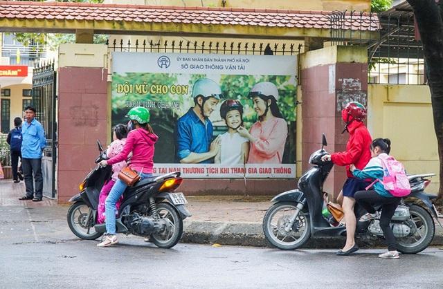 Phóng viên Dân trí ghi nhận tại một số trường Tiểu học trên địa bàn Thủ đô Hà Nội, các phụ huynh khi đưa con đến trường đều đội mũ bảo hiểm nhưng lại không đội mũ bảo hiểm cho con.