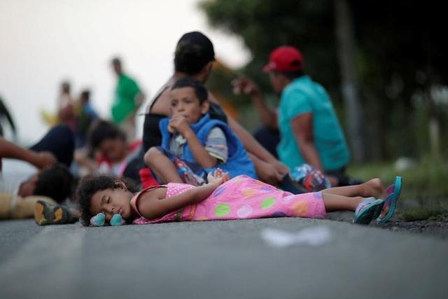 Một em nhỏ ngủ ngay trên đường khi cùng gia đình đi tị nạn. (Ảnh: Reuters)