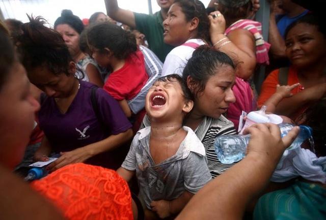 Những đứa trẻ theo cha mẹ đi tị nạn. (Ảnh: Reuters)