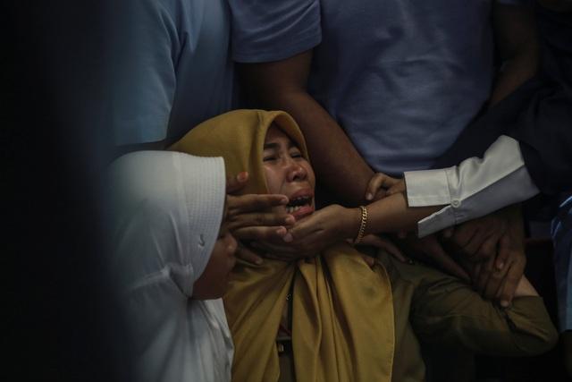 Thân nhân không giấu nổi đau buồn khi nhận được tin dữ. (Ảnh: Reuters)