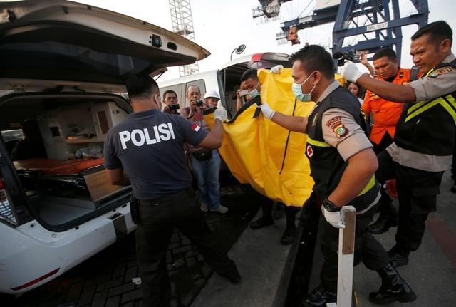 Thi thể nạn nhân được đặt trong túi đựng xác chuyển lên xe.