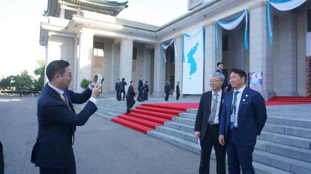 Chủ tịch LG Group Koo Kwang-mo chụp Chủ tịch Tập đoàn SK Hàn Quốc Chey Tae-won và ông Kim Hyun-chul - thư ký tổng thống Hàn Quốc phụ trách các vấn đề kinh tế bên ngoài một tòa nhà tại Triều Tiên.