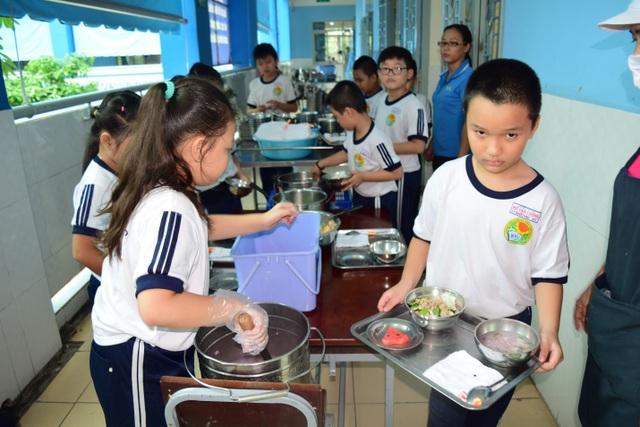 Các em học sinh trường tiểu học Hồ Văn Cường (Q. Tân Phú – TP. HCM) cùng chuẩn bị bữa trưa với thực đơn được chuẩn bị bằng phần mềm.