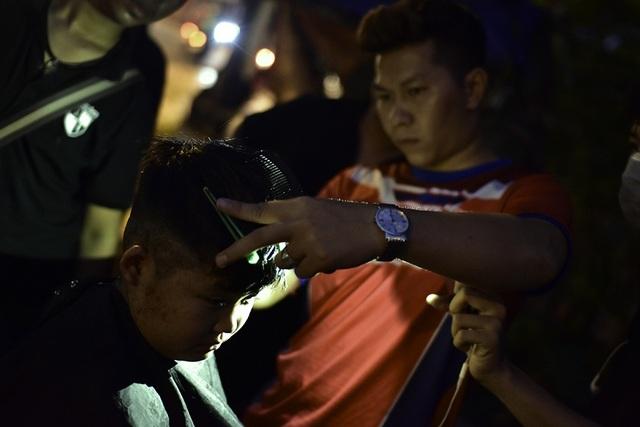 Hình ảnh khá lạ khi những anh thợ hớt tóc trên vỉa hè bằng đèn flash điện thoại
