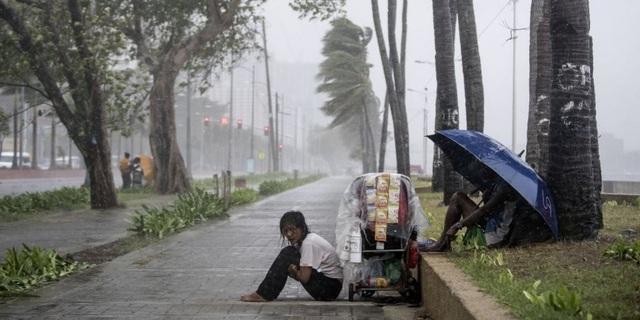 Một người bán hàng rong ngồi co ro trong cơn bão (Ảnh: AFP)